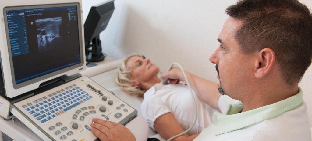 Arzt führt eine Ultraschalluntersuchung am Hals der Patientin aus