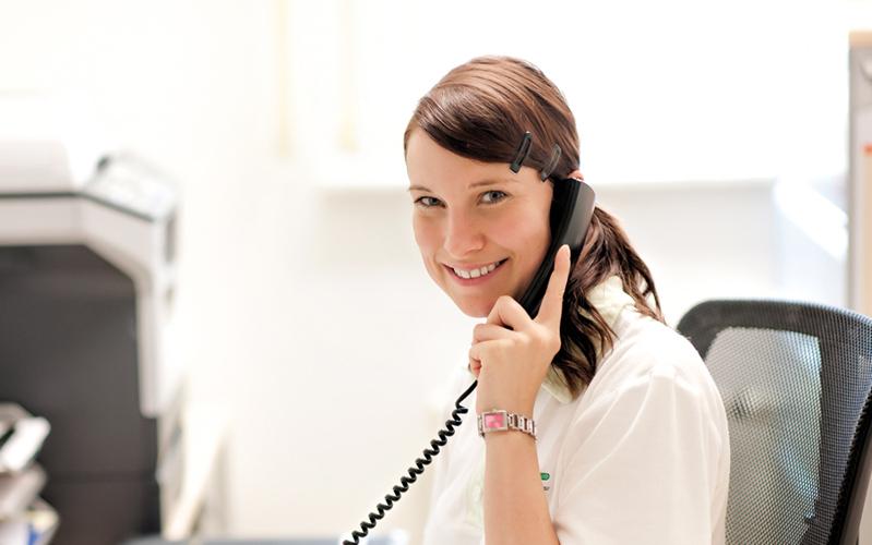 Junge Frau mit Telefonhörer am Ohr