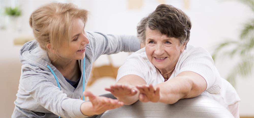 Physiotherapeutin arbeitet mit älterer Patientin