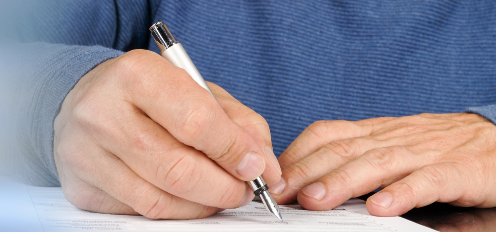 Hände halten einen Füller und beschreiben ein Blatt